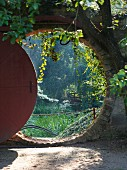 View through round doorway into lush garden