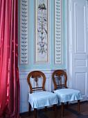 Zwei Stühle vor Wand mit bemalter Kassettenverkleidung