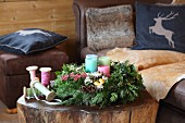 Advent arrangement with four candles on tree-stump coffee table