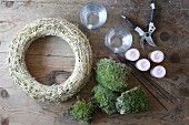 Moss wreath, Christmas baubles and Advent candles in glas containers
