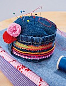 A denim pin cushion with colourful fabric stripes