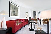 Two dogs on red sofa in living room with curved wall