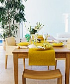 Felt runner and yellow crockery on wooden table