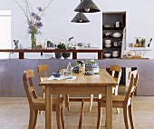 Oak table and chairs in front of elegant kitchen counter and stacked crockery on shelves in niche