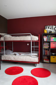 Bunk beds and bookcase in children's bedroom with dark red walls and round red rugs