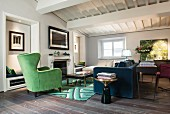 Green wing-back chair and blue sofa with console table against back in interior with white wood-beamed ceiling