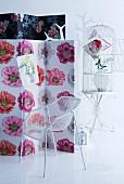 Paravent mit Blumenstoff bezogen, weisser Designerstuhl aus Metall, Garderobenbaum und Vogelkäfig