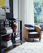 Armchair with leather seat cushion next to open black shelving and white flokati rug