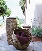 Verschiedene Korbgefäße auf Natursteinbelag neben Lavendeltopf an Hauswand