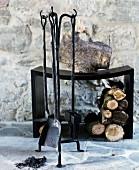 Brennholz unter schwarzem, modernem Hocker, davor rustikales Kamingeschirr