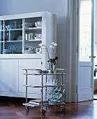Elegant serving trolley next to white dresser