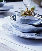 Festliches Gedeck mit Beerendekoration auf weißem Tischset