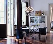 Eleganter Essbereich mit schwarzen Korbstühlen und Kronleuchter vor Fenstertür