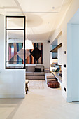 Open doorway leading into living room with glass wall panel and wall hanging