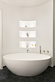 Oval free-standing bathtub against curved wall with niches