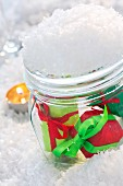 Small wrapped gifts in snow-covered mason jar