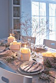 Wintry, romantic dinner table decorated with lit candles in chip wood baskets