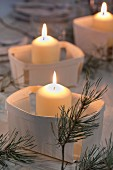 Lit candles in chip wood baskets and fir sprigs decorating table