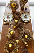 Several rustic wreaths and gold candles decorating festive table