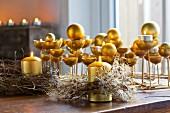Goldfarbene Kerzenständer mit Kerzen und Kugeln und rustikale, getrocknete Kränze