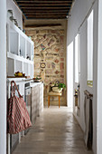 White shelves and mosaic wall in narrow kitchen