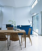 Wooden table, various chairs, blue sofa, high ribbon window and fireplace in open-plan interior