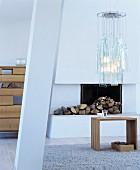 Holzhocker als Beistelltisch vor weißem, offenem Kamin unter Pendelleuchte