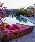Rattan lounger with hot-pink cushions and scatter cushions in front of swimming pool