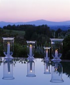 Lit candle lanterns reflected in surface of water in front of Mediterranean landscape