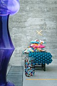 Murano glass vase in front of stack of colourful cushions and petrol-blue felt ball rug on stool in front of concrete wall