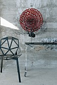 Black sea fan coral and red glass dish on designer table next to black metal chair