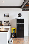 Black fridge against white wall in kitchen
