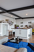 View past sofa into kitchen in open-plan industrial-style interior