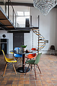 Round dining table and colourful designer chairs in industrial loft apartment