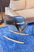 Blue designer rocking chair on bright blue rug