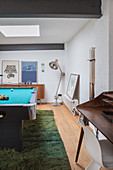 Pool table on green rug in masculine games room
