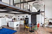 Open-plan kitchen and round dining table with designer chairs in industrial loft apartment