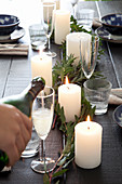Hand pouring Champagne into glass on festively set table