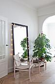 Skandinavischer Designerstuhl vor einem Spiegel mit Lichterkette