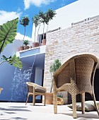 Wicker chair outside modern house with stone wall and waterfall