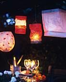Verschiedene Papierlaternen über gedecktem Tisch im abendlichen Garten