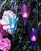 Purple and blue conical tealight holders on ivy-covered garden wall