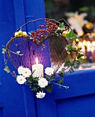 Pillar candle in wire love-heart decorated with ivy, branches and berries decorating summer garden