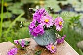 Sträusschen mit Herbstanemonen und Fenchelgrün auf Tisch im Garten