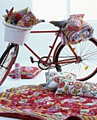 Red bicycle and floral textiles arranged for indoor picnic