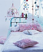 Romantic bed with canopy and hippy-style lamp