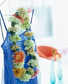 Necklace of flowers hung on blue dress