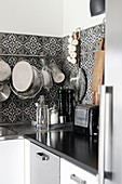 Kitchen utensils hung from rod on ornate, black-and-white, tiled splashback