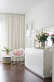 Vase of flowers and transparent table lamp on white chest of drawers, classic rocking hair and side table next to window with curtains