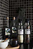 Spices against black mosaic-tiled wall